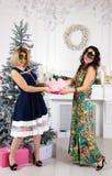 Retrato de mujeres felices elegantes en las máscaras de la Navidad que sostienen las actuales cajas mientras que coloca y mira la imagenes de archivo