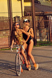 Retrato de mujeres jovenes bastante atractivas en trajes de baño con la bicicleta Imagen de archivo