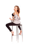 Retrato de mulheres bonitas no estúdio, sentando-se em uma cadeira da barra no un Fotos de Stock
