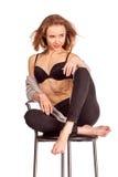 Retrato de mulheres bonitas no estúdio, sentando-se em uma cadeira da barra no un Imagens de Stock Royalty Free