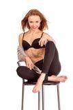 Retrato de mulheres bonitas no estúdio, sentando-se em uma cadeira da barra no un Foto de Stock Royalty Free