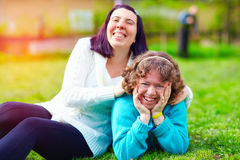 Retrato de mulheres felizes com inabilidade no gramado da mola imagens de stock
