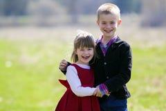 Retrato de niños sonrientes rubios hermosos con los dientes divertidos del niño en la ropa elegante que se une al aire libre en b Imagen de archivo libre de regalías