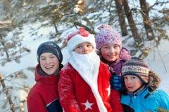 Retrato de niños y de Papá Noel en bosque del invierno Fotografía de archivo libre de regalías