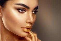 Retrato de oro de la cara de la mujer de la piel del arte de la moda imagen de archivo