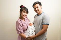 Retrato de padres asiáticos y de seis meses del bebé en casa Foto de archivo