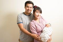 Retrato de padres asiáticos y de seis meses del bebé en casa Foto de archivo libre de regalías