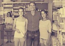 Retrato de padres con compras del adolescente de la hija en stor de la droga Foto de archivo