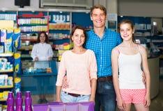 Retrato de padres con compras del adolescente de la hija en stor de la droga Fotografía de archivo