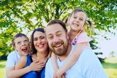 Retrato de padres felices con dos pequeños niños Imagen de archivo libre de regalías