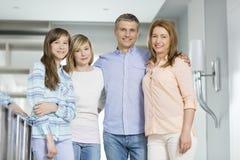 Retrato de padres felices con las hijas que se unen en casa Fotografía de archivo libre de regalías