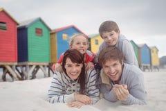 Retrato de padres felices con los niños que mienten en la arena Imagenes de archivo
