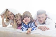 Retrato de padres felices y de niños que mienten bajo cubierta de cama imagen de archivo