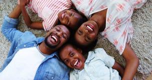 Retrato de padres felices y de niños que mienten en la manta almacen de metraje de vídeo