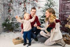 Retrato de pais novos felizes positivos com seu filho pequeno em Foto de Stock