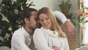 Retrato de pares alegres en el amor que se sienta cerca del árbol de navidad en casa La esposa y el marido son felices juntos Amo metrajes
