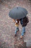Retrato de pares con el paraguas en lugar de los adoquines en la ciudad Foto de archivo libre de regalías