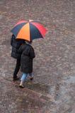 Retrato de pares con el paraguas en lugar de los adoquines en la ciudad Fotografía de archivo