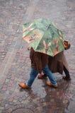 Retrato de pares con el paraguas en lugar de los adoquines en la ciudad Imagen de archivo