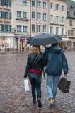 Retrato de pares con el paraguas en lugar principal de los adoquines en la ciudad Fotos de archivo