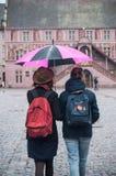 Retrato de pares con el paraguas rosado en lugar de los adoquines en el ci Fotografía de archivo
