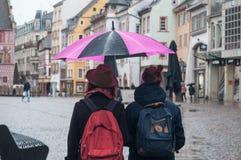 Retrato de pares con el paraguas rosado en lugar de los adoquines en la ciudad Foto de archivo libre de regalías