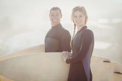 Retrato de pares con la tabla hawaiana que se coloca en la playa Fotos de archivo libres de regalías
