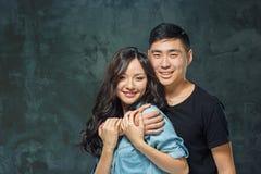 Retrato de pares coreanos de sorriso em um cinza imagem de stock royalty free