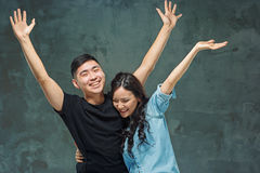 Retrato de pares coreanos sonrientes en un gris Foto de archivo libre de regalías