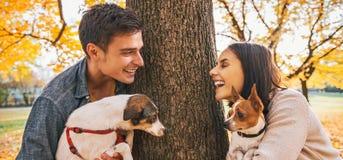 Retrato de pares felices con los perros al aire libre en parque del otoño Fotografía de archivo libre de regalías