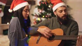 Retrato de pares felices en los sombreros de Papá Noel que cantan canciones en casa Hombre que toca la guitarra Mujer con la guir metrajes