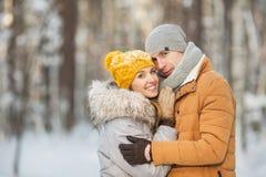 Retrato de pares felices jovenes en un color gris y anaranjado de la ropa en un bosque del invierno Foto de archivo libre de regalías