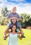 Retrato de pares felizes junto com o adolescente Fotografia de Stock Royalty Free