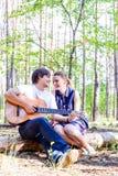 Retrato de pares felizes loving novos com a guitarra na floresta fotografia de stock royalty free