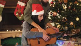 Retrato de pares felizes nos chapéus de Santa na Noite de Natal Mulher de ensino do homem para jogar a guitarra ?rvore de Natal n video estoque