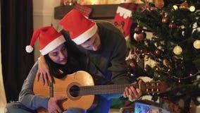 Retrato de pares felizes nos chapéus de Santa na Noite de Natal Mulher de ensino do homem para jogar a guitarra ?rvore de Natal n filme