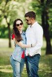 Retrato de pares felizes novos no amor, sorrindo e abraçando no jardim fotos de stock