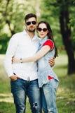 Retrato de pares felizes novos no amor, sorrindo e abraçando no jardim imagens de stock