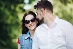 Retrato de pares felizes novos no amor, sorrindo e abraçando no jardim imagens de stock royalty free
