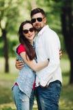 Retrato de pares felizes novos no amor, sorrindo e abraçando no jardim fotos de stock royalty free