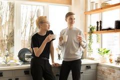 Retrato de pares gay internacionales en ropa casual por la mañana en casa en la cocina foto de archivo