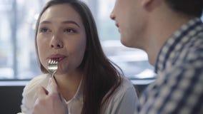 Retrato de pares jovenes en el café moderno que disfruta del tiempo junto cercano para arriba Hombre irreconocible que alimenta a almacen de video