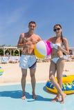 Retrato de pares jovenes en la playa con la pelota de playa Fotos de archivo libres de regalías