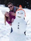 Retrato de pares jovenes felices con el muñeco de nieve Imágenes de archivo libres de regalías