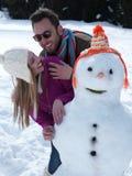 Retrato de pares jovenes felices con el muñeco de nieve Fotos de archivo