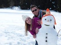 Retrato de pares jovenes felices con el muñeco de nieve Foto de archivo