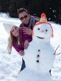 Retrato de pares jovenes felices con el muñeco de nieve Fotos de archivo libres de regalías