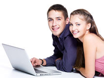 Retrato de pares jovenes felices con la computadora portátil foto de archivo