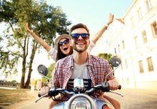 Retrato de pares jovenes felices en la vespa que disfruta de viaje por carretera Imagen de archivo libre de regalías