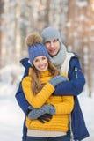Retrato de pares jovenes sonrientes en un bosque en el invierno Foto de archivo libre de regalías